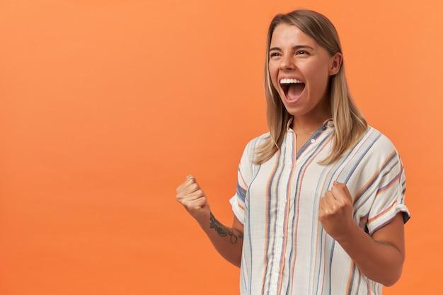 Gelukkig opgewonden jonge vrouw in gestreept shirt met overwinningsgebaar en schreeuwend geïsoleerd over oranje muur
