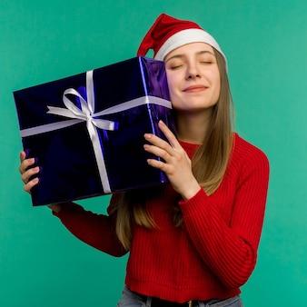 Gelukkig opgewonden jonge vrouw in kerstman hoed met geschenkdoos op blauwe achtergrond - afbeelding