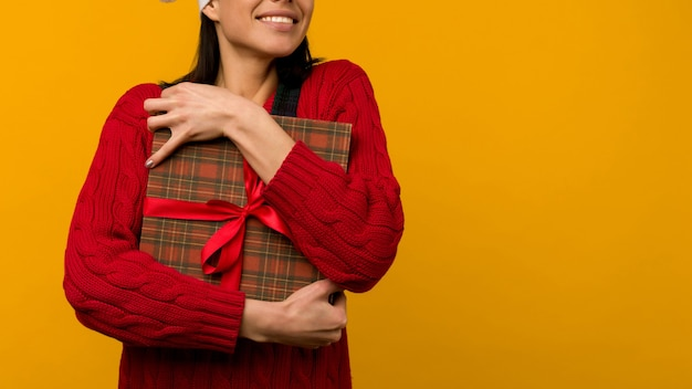 Gelukkig opgewonden jonge vrouw in kerstman hoed met geschenkdoos op gele achtergrond - afbeelding