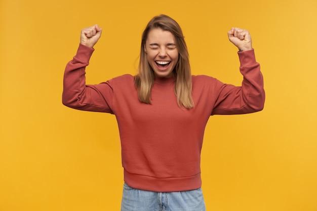Gelukkig opgewonden jonge vrouw in vrijetijdskleding met opgeheven handen en vuisten schreeuwen en vieren overwinning op gele muur
