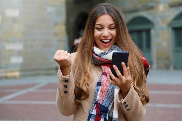 Gelukkig opgewonden jonge vrouw lacht kijken naar goed nieuws op mobiele telefoon met vuist omhoog in stad straat, wintertijd