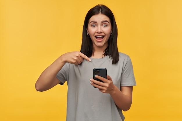 Gelukkig opgewonden jonge vrouw met donker haar en geopende mond in grijze t-shirt ziet er verbaasd uit en wijst naar mobiele telefoon over gele muur