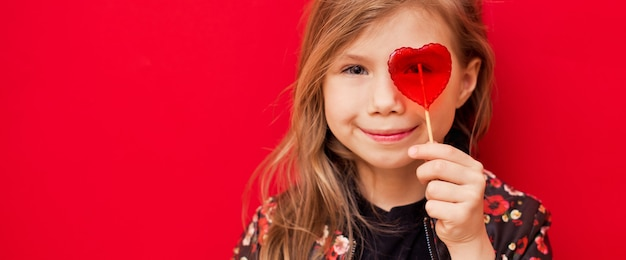 Gelukkig opgewonden kindmeisje bedekte haar oog met heldere hartvormige lolly op rode achtergrond