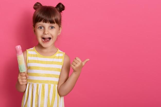 Gelukkig opgewonden klein kind met ijs met wijd geopende mond, wijzende duim opzij, grappig meisje met knopen, kopie ruimte voor reclame.
