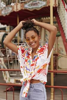 Gelukkig opgewonden krullende brunette vrouw in denim broek, stijlvolle bijgesneden kleurrijke blouse en oranje zonnebril raakt haar, glimlacht en poseert in de buurt van carrousel
