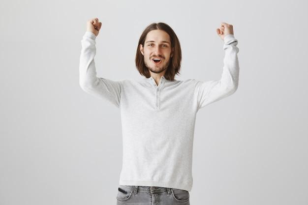 Gelukkig opgewonden man die zich verheugt op goed nieuws