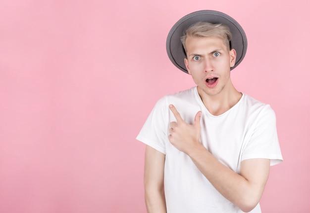 Gelukkig opgewonden man in hoed wijzend op kopie ruimte met vinger geïsoleerd op roze achtergrond