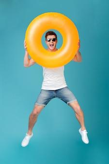 Gelukkig opgewonden man in zonnebril opblaasbare ring houden en springen