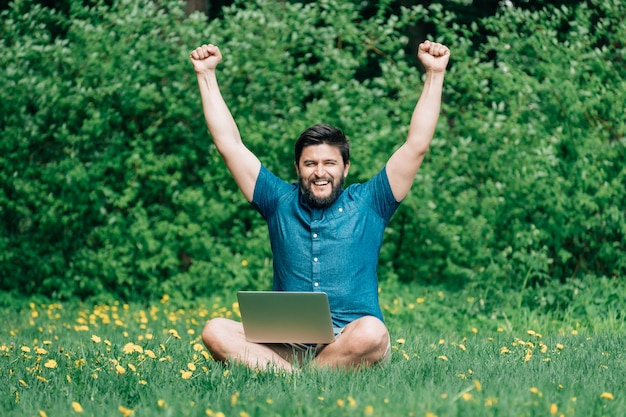 Gelukkig opgewonden man met laptop opgeheven handen vieren succes