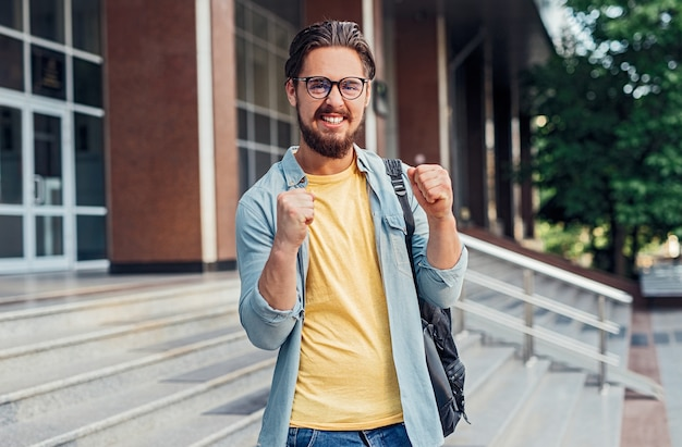 Gelukkig opgewonden mannelijke student examen pass vieren