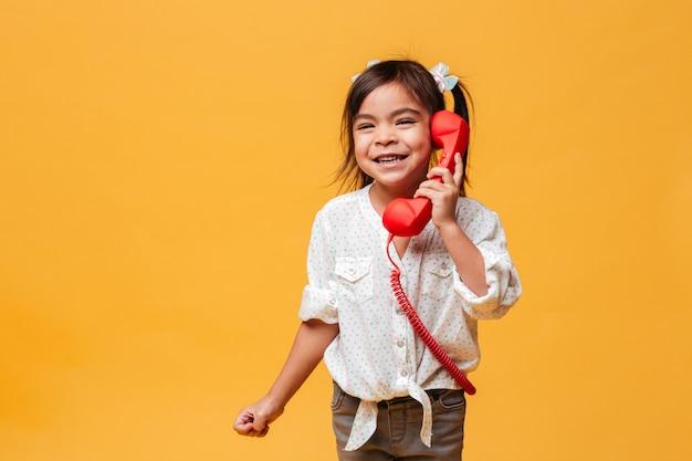 Gelukkig opgewonden meisje kind praten door rode retro telefoon.
