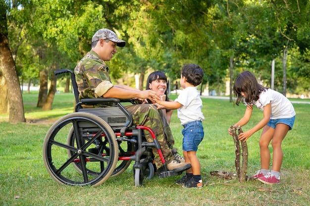 Gelukkig opgewonden moeder en gehandicapte militaire vader in rolstoel vrije tijd doorbrengen met kinderen buitenshuis, brandhout regelen voor vuur op gras. gehandicapte veteraan of familie buitenshuis concept