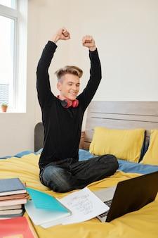 Gelukkig opgewonden student zittend op bed en armen opheffen na het passeren van de programmeertest online