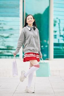 Gelukkig opgewonden vietnamees tienermeisje in minirok die zich voor winkelcomplex bevindt