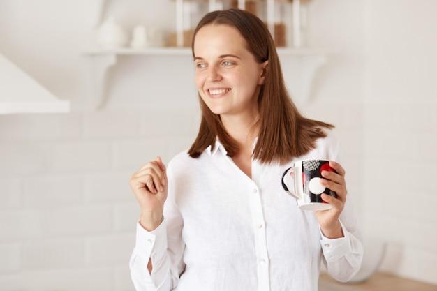 Gelukkig opgewonden vrouw die vroeg in de ochtend wakker wordt, met een kopje koffie of thee in handen staat en danst, een goed humeur heeft, poserend met een keuken op de achtergrond.