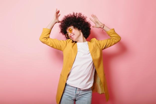 Gelukkig opgewonden vrouw met kort krullend haar gekleed gele jas en stijlvolle bril dansen op roze met opgeheven handen