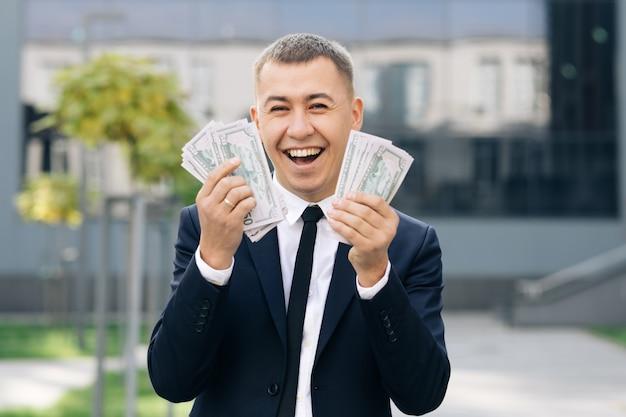 Gelukkig opgewonden zakenman met geld - amerikaanse dollar biljetten