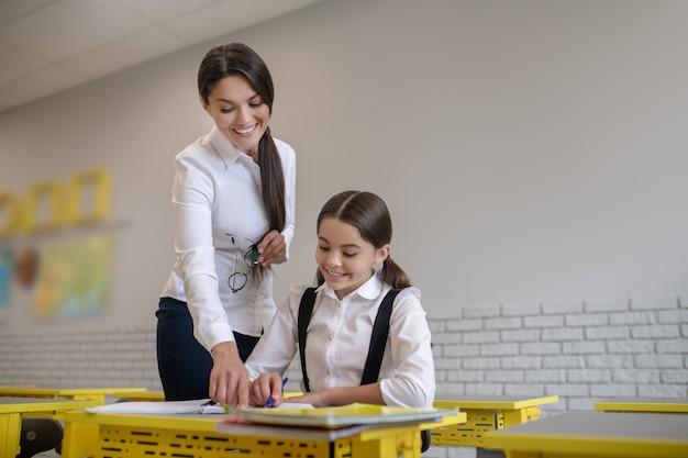 Gelukkig oprechte langharige vrouwelijke leraar wijzend op notitieboekje van schoolmeisje zit aan haar bureau