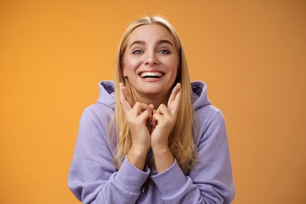 Gelukkig optimistisch schattig positief glimlachend blond meisje grijnzend opgewonden kruis vingers maken wens dromen verlangen uitkomen anticiperend op goed nieuws bidden oranje achtergrond wachten resultaten.