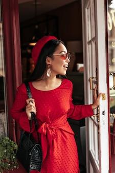Gelukkig optimistische brunette vrouw in stijlvolle rode jurk, trendy baret en zonnebril houdt zwarte handtas vast, glimlacht en opent de deur