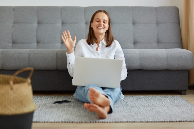 Gelukkig optimistische vrouw met een wit overhemd en een spijkerbroek die in de buurt van de bank in de woonkamer zit, naar een laptop-webcamera kijkt en met de hand zwaait, hallo of tot ziens zegt, met een videogesprek.