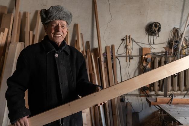 Gelukkig oude man in zwarte jas houdt in zijn handen houten plank