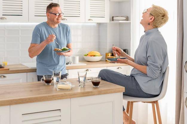Gelukkig ouder paar eten ontbijt samen praten en lachen goedemorgen in het pensioenleven
