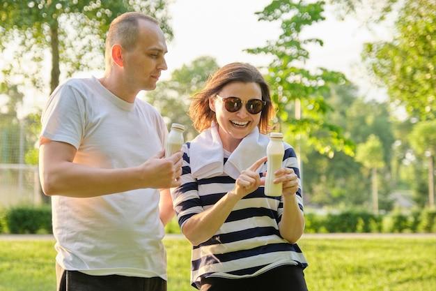 Gelukkig ouder paar in park, drinkyoghurt rusten