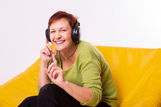 Gelukkig oudere luisteren muziek op koptelefoon