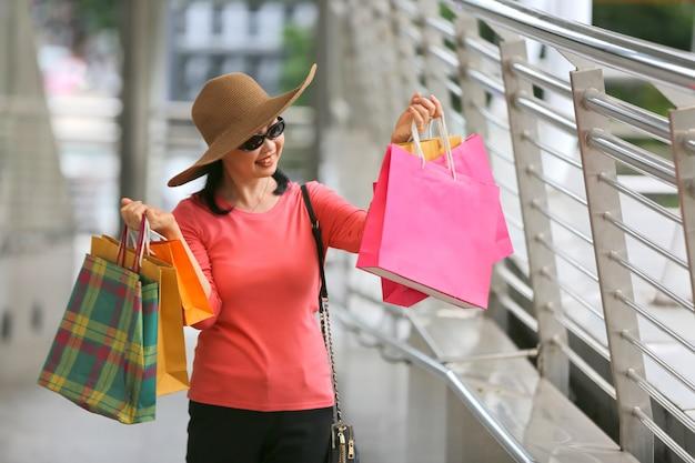 Gelukkig oudere man en vrouw lopen op straat in een zomerse dag. ontspannen senior paar met hoeden gaan winkelen.