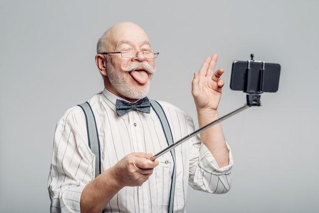 Gelukkig oudere man maakt selfie op telefoon. rijpe oudste die zijn tongen toont bij camera