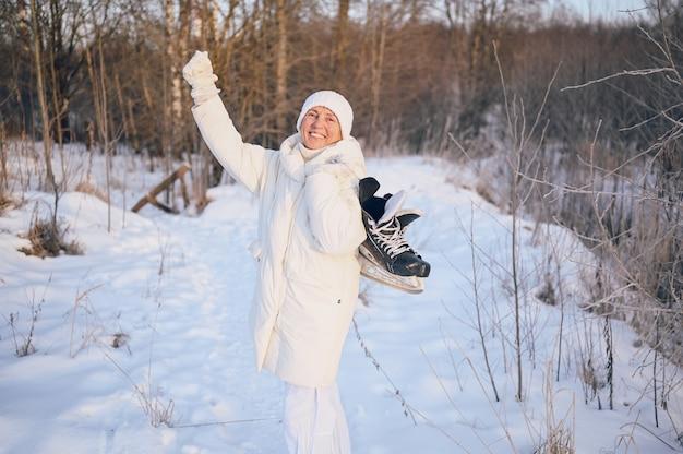 Gelukkig oudere senior rijpe vrouw in witte warme uitloper spelen met ijs-of rolschaatsen in zonnige besneeuwde winter buiten