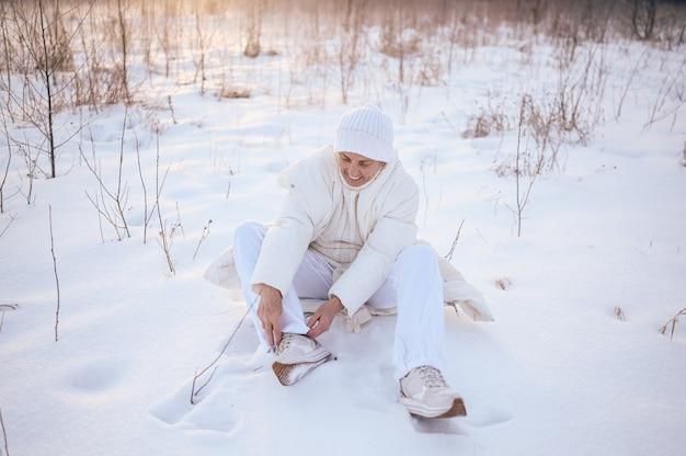Gelukkig oudere senior rijpe vrouw in witte warme uitloper spelen met sneeuw in zonnige winter buiten