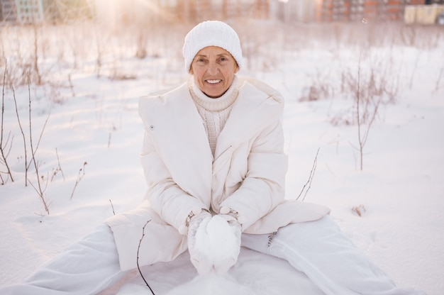 Gelukkig oudere senior rijpe vrouw in witte warme uitloper spelen met sneeuw in zonnige winter buiten.