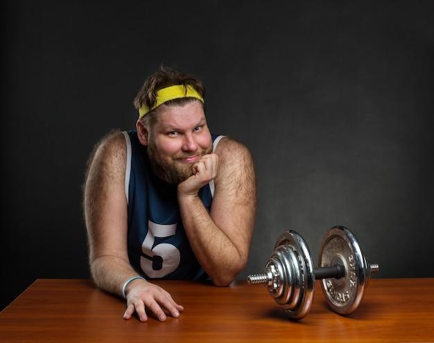 Gelukkig overgewicht man met een halter aan tafel