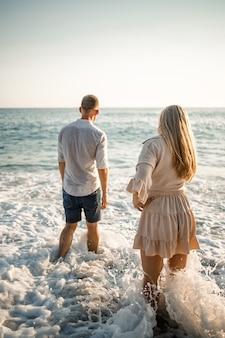 Gelukkig paar aan zee. liefhebbers van huwelijksreizen. man en vrouw op het eiland. mooie paar plezier aan de kust. gelukkig paar op vakantie. man en vrouw aan zee.