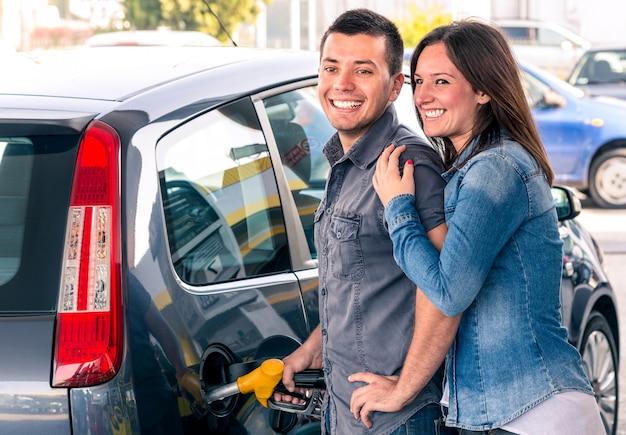 Gelukkig paar bij de benzinepomp pompende benzine bij benzinepomp