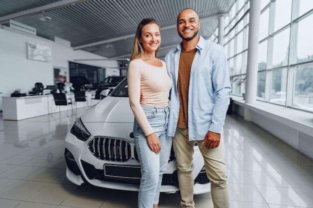 Gelukkig paar blanke vrouw en afro-amerikaanse man permanent in de buurt van hun nieuwe auto