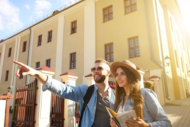 Gelukkig paar dat buiten sightseeing loopt en een kaart vasthoudt.