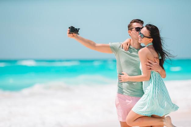 Gelukkig paar dat een foto op wit strand op wittebroodswekenvakantie neemt