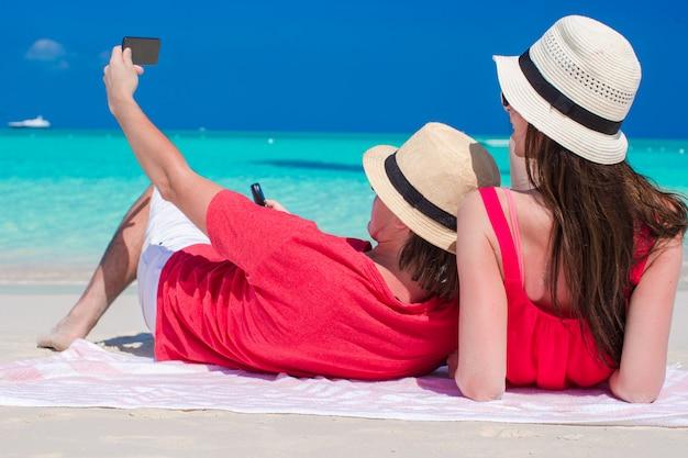 Gelukkig paar dat een foto zelf op tropisch strand neemt