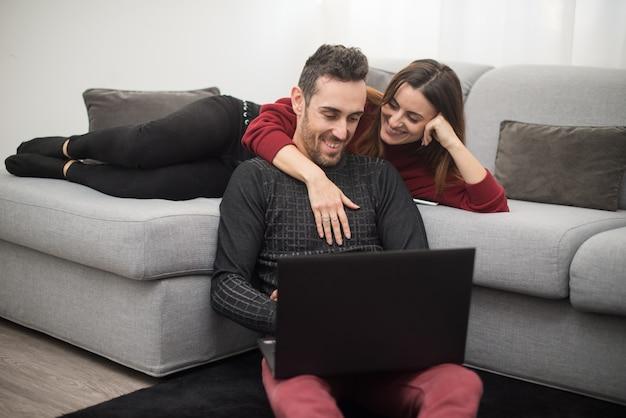 Gelukkig paar dat een laptop computer in hun huis met behulp van