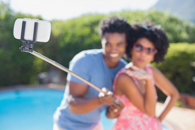 Gelukkig paar dat een selfiestok gebruikt