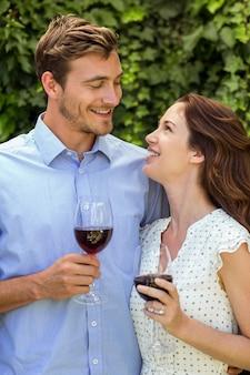 Gelukkig paar dat elkaar bekijkt terwijl het houden van wijnglazen