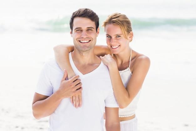Gelukkig paar dat elkaar op het strand omhelst