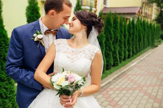 Gelukkig paar dat en hun neuzen glimlacht raakt. het boeket van de bruidholding
