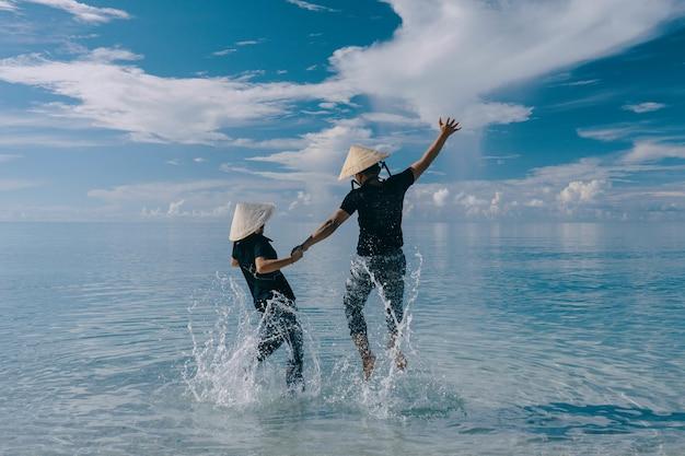 Gelukkig paar dat hoeden draagt die in het water springen