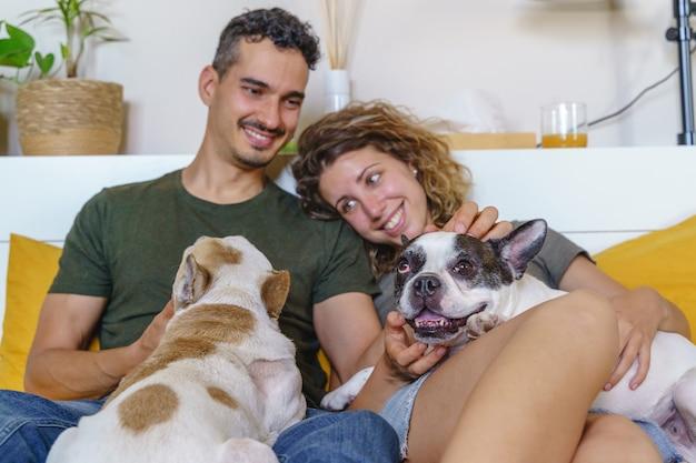 Gelukkig paar dat met hond thuis speelt. horizontale zijaanzicht van paar lachen met bulldog in bed.