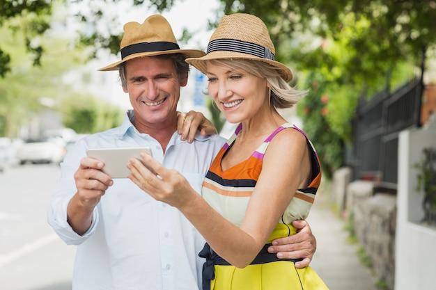 Gelukkig paar dat mobiele telefoon bekijkt