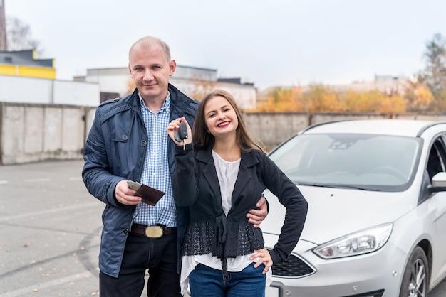 Gelukkig paar dat nieuwe auto koopt die buitenshuis poseert